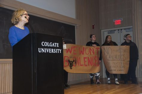 Conservative author and commentator Heather Mac Donald in front of protesters at her lecture. These two signs were one of about six large signs that went up in the crowd during the Q&A section of the lecture, along with smaller posters.