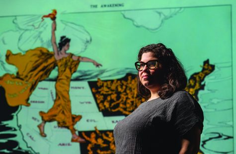 Monica Mercado, Assistant Professor of History, stands with a projection of The Awakening, an image of Lady Liberty about women's suffrage by Henry Mayer, November 6, 2020.